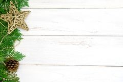 The Pine leaf with yellow gold star and christmas ball decoratio. N on white wooden board with copy space , happy new year and chistmas festival background Stock Images