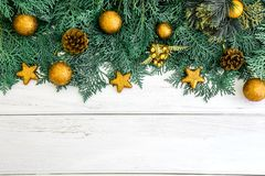 The Pine leaf with yellow gold star and christmas ball decoration on white wooden board with copy space , happy new year and chist. Pine leaf with yellow gold Royalty Free Stock Photography
