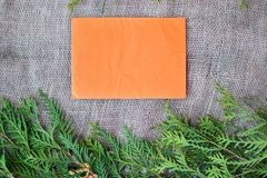 Winter holiday invitation. Pine leaves on the edges of rustic burlap and orange paper Royalty Free Stock Image