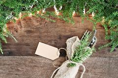 Pine Needles and Lights with Silverware and Card over Wooden Bac. Christmas tree pine branches, silverware wrapped in a burlap napkin with blank card and stock image