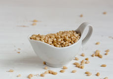 Pine nuts. In a gravy boat on the table Stock Image