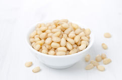 Pine nuts in a bowl on a white background Royalty Free Stock Photos