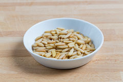 Pine nuts in a bowl on wood Royalty Free Stock Image