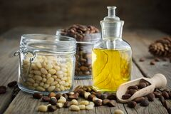 Free Pine Nuts Essential Oil Bottle And Jars Of Cedar Pine Nuts Royalty Free Stock Images - 170137599