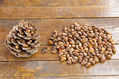 Pine nuts and pine cone on wooden table Stock Photo