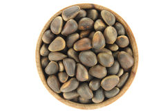 Pine nuts in a round wooden form. On a white background Royalty Free Stock Images