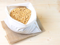 The pine nuts in a white cotton bag on a wooden table Stock Photo