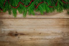 Pine tree border with red garland on old wooden background Royalty Free Stock Images