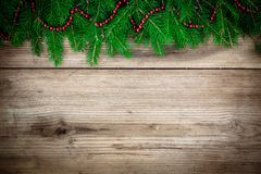 Pine tree border with red garland on old wooden background Stock Photo