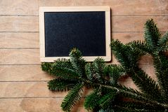 Pine tree branch and blackboard. On wooden table. Side view royalty free stock photo