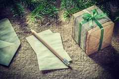 Pine tree branch handmade gift box paper pencil on sacking backg. Round Royalty Free Stock Photo