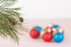 Pine tree branch with red, blue and gold Christmas baubles background Stock Images
