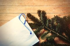 Pine tree branch and shopping bag. On wooden table. Side view stock photography