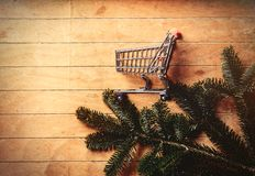Pine tree branch and shopping cart. On wooden table. Side view stock photography