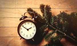 Pine tree branch and vintage alarm clock. On wooden table. Side view royalty free stock photography