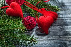 Pine tree branches red hearts balls on wooden board.  stock photos