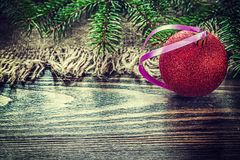 Pine tree branches sacking Christmas ball on wooden board.  Royalty Free Stock Photos