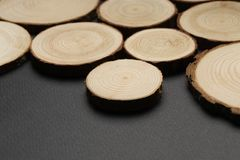 Pine tree cross-sections with annual rings on plane black surface. Lumber piece close-up. Pine tree cross-sections with annual rings on plane black surface royalty free stock photography