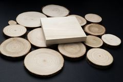 Pine tree cross-sections with annual rings and wooden square on black surface. Lumber piece close-up, top view. Pine tree cross-sections with annual rings and royalty free stock images