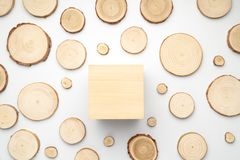 Pine tree cross-sections with annual rings and wooden square on white background. Lumber piece close-up, top view. Pine tree cross-sections with annual rings stock photo