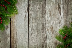 Pine tree with red garland on old wooden background Stock Photos