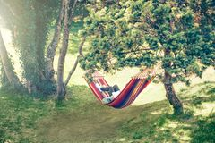 Summer relaxing outdoors reading. Pine trees green park summer woman laying in hammock rading a book Royalty Free Stock Photos