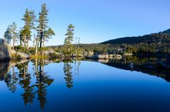 Pine trees, rocks, and perfect blue sky reflected in the serene, calm, and peaceful waters of an alpine lake at sunrise royalty free stock photo