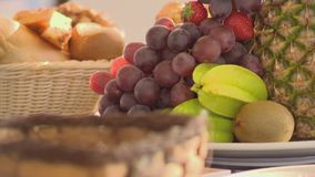 Pineaple, grapes, kiwi, strawberry focus in on a table. stock video