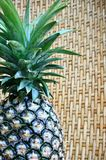 Pineapple. Fresh tropical pineapple on weaved bamboo background royalty free stock photography