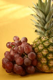 Pineapple. And grapes on yellow background Stock Photography