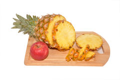 Pineapple and apple. Lay on a wooden board Stock Images