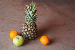 Pineapple, apple and oranges. On wooden background Stock Images