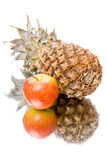 Pineapple and apple with reflection Stock Images