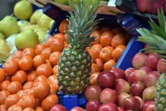 Pineapple, apples and tangerines. In the vegetable market Stock Photography