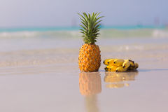 Pineapple and bananas on the beach. On blue sea background stock photography