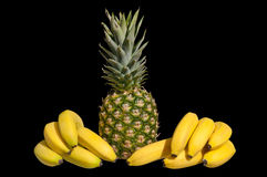 Pineapple with bannannas. Pineapple between bannannas on a black background royalty free stock image