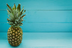 Pineapple on a blue wooden table Stock Image