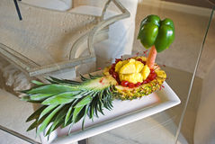 Pineapple Boat5. An appetizer dish of a carved pineapple boat with cherries and pineapple chunks on a glass table Royalty Free Stock Photo