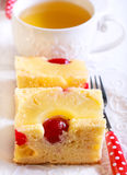 Pineapple and cherry cake, sliced. And cup of  tea Stock Photo
