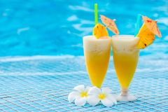 Pineapple cocktail beautifully decorated with umbrellas. And flowers on the edge of the pooll royalty free stock images