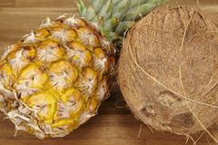 Pineapple and coconut on an acacia tabletop - close shot Stock Photo