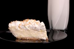 Pineapple coconut cream pie with toasted coconut and milk. On a black plate Royalty Free Stock Images