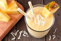 Pineapple coconut smoothie above scene against wood Stock Photos