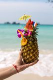 Pineapple coctail. In a woman's hand infront of the sea Stock Photos