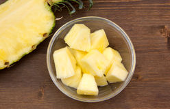 Pineapple cubes on wooden bowl on top Stock Photography