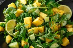 Pineapple Cucumber salad with wild green rocket, lime and olive oil. Healthy juicy food stock photo
