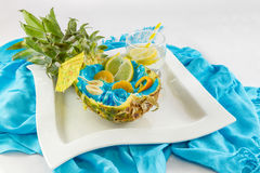 Pineapple cut in half with sliced fruit and lemon coctail side v Royalty Free Stock Images