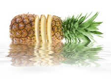 Pineapple with cut slices. A juicy pineapple sitting in a pool of water with reflection Royalty Free Stock Photos