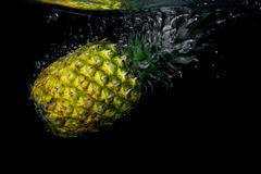 Pineapple falling in water on black background stock images