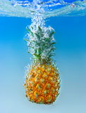 Pineapple falls into wate Royalty Free Stock Image